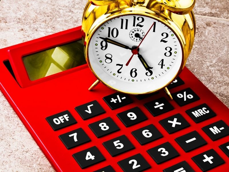 a clock on top of a calculator to depict time conversion