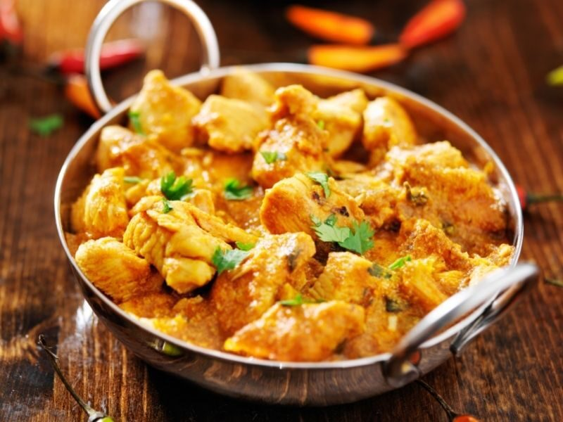 Chicken Curry Recipe in silver Balti style dishes with bowls of rice on a wooden table