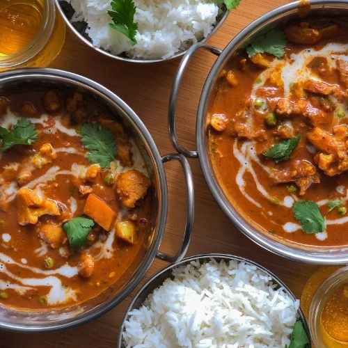 Vegan Curry Recipe in silver balti stle dishes with bowls of rice on a wooden table