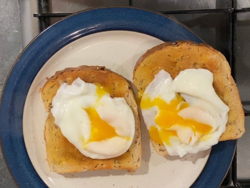 two poached eggs on wholemeal toast with the yolk popped